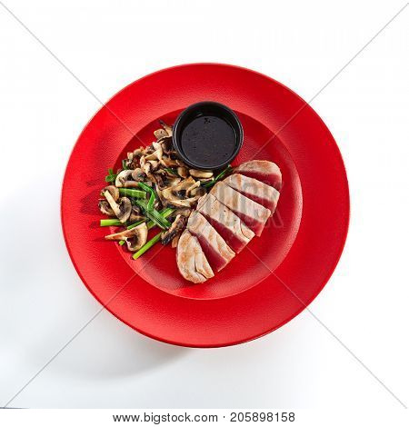 Teppanyaki Japanese and Korean Grill Food - tuna with vegetables mushrooms with sauce on red plate on  white isolated background. Asian menu. Top View