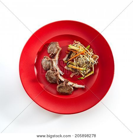 Teppanyaki Japanese and Korean Grill Food - Rack of Lamb with vegetables, noodles and sesame seeds on red plate with sauce. Asian menu