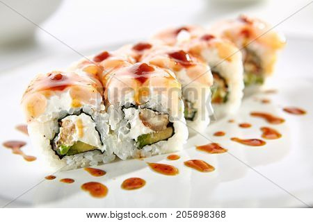 Katei rolls with shrimp, eel, Philadelphia cheese and avocado served on white flat plate. Asian menu for gourmets in luxury restaurant
