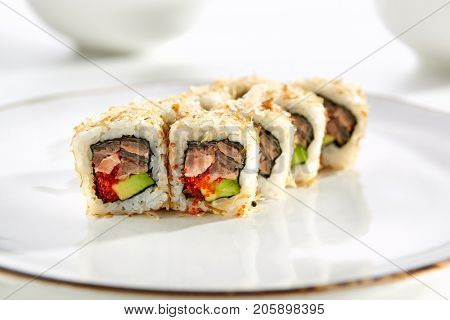 Sushi rolls with salmon and avocado served on white flat plate. Asian menu for gourmets in luxury restaurant