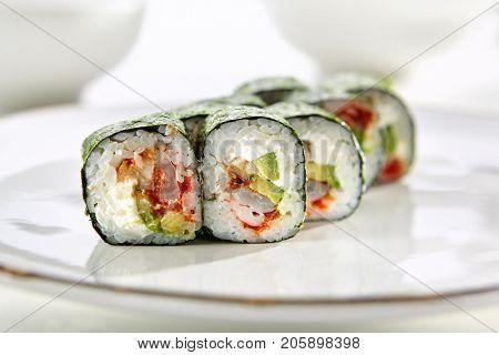 Kimasu rolls with shrimp, eel, avocado, tobiko caviar and Philadelphia cheese served on white flat plate. Asian menu for gourmets in luxury restaurant