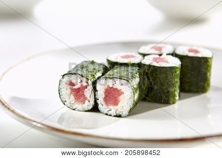 Classic tuna maki rolls served on white flat plate. Asian menu for gourmets in luxury restaurant