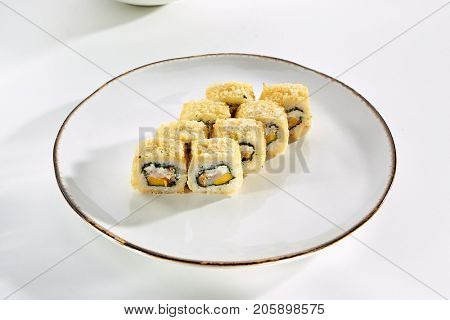 Hot rolls with salmon, avocado, Philadelphia cheese, baked in panko breadcrumbs served on white flat plate. Asian menu for gourmets in luxury restaurant