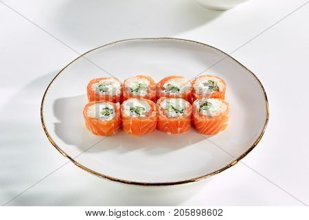 Miyazaki rolls with salmon, cucumber and sesame seeds and Philadelphia cheese served on white flat plate. Asian menu for gourmets in luxury restaurant