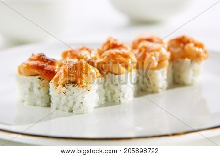 Baked rolls with scallop tar-tar, spicy sauce, cream cheese and mango with rice on white plate with gold border. Asian menu