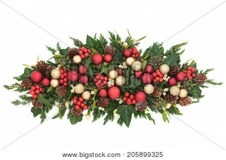 Christmas decorative centrepiece with red and gold bauble decorations, holly, ivy, mistletoe, fir and pine cones on white background.