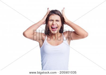 unhappy screaming young beautiful woman wearing jeans against white studio background