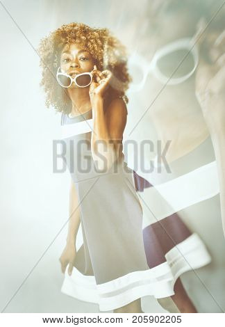 African Caribbean Woman with afro hair with vintage seventies clothing dancing and wearing sunglasses - trendy double exposure