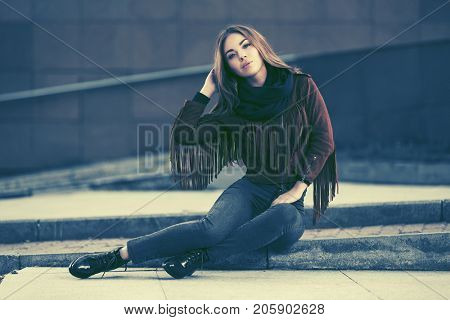 Happy young woman sitting on the sidewalk in city street. Stylish fashion model in leather fringe suede jacket and blue jeans