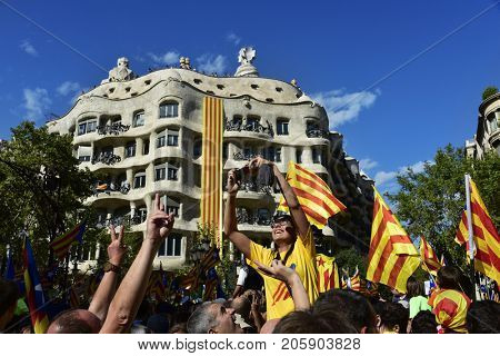 BARCELONA, SPAIN - SEPTEMBER 11, 2017: People in Barcelona, Spain, partaking in a rally in support for the independence of Catalonia, highlighting the famous Casa Mila or La Pedrera in the background
