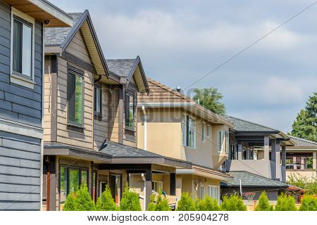 A perfect neighborhood. Houses in suburb at Summer in the north America. Top of a luxury houses with nice window over blue sky.