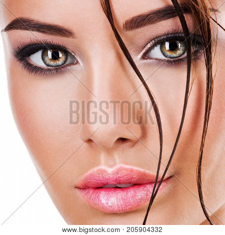 Closeup face of beautiful woman with dark brown eye makeup. Macro portrait of female eyes with long eyelashes and long wet locks on the face.