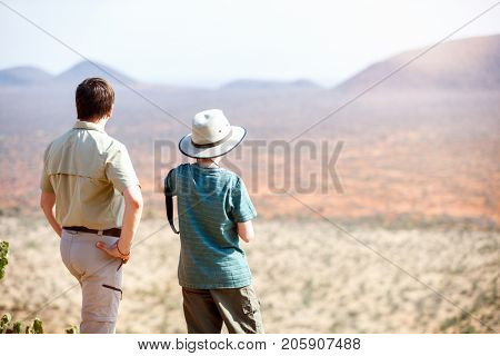 Family of father and child on African safari vacation enjoying view over Samburu Kenya