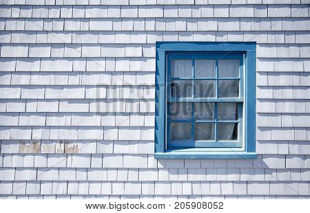 blue window frame on a white wooden wall background outside. part of the wall of the house with a window. Siding of the house from the wooden plank. Copy space for your text