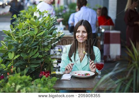 Young beautiful brunette woman in a turquoise suit is sitting in a restaurant