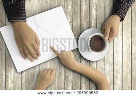 Father's Day. Hands of little kid and his father pointing at an empty greeting card on the table while holding a cup of coffee