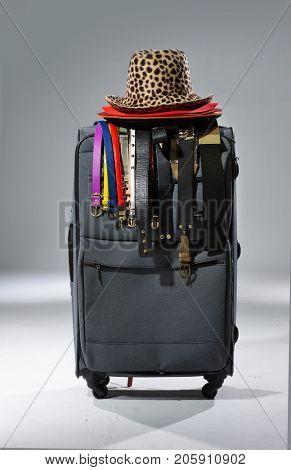 Set of luggage, hat and belt isolated on light background