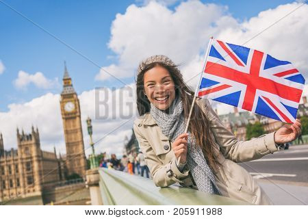 London travel tourist woman showing Union flag Great Britain british UK flag. Asian girl at Big Ben on Westminster bridge on Europe holidays holding icon at iconic landmark.