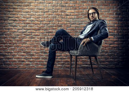 Imposing young man in elegant suit sitting on a chair in a modern interior. Fashion. Business.