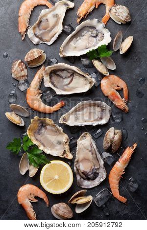 Fresh seafood on stone table. Oysters, prawns and scallops. Top view