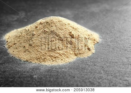 Heap of maca powder on dark  background