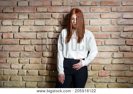 Young ginger woman standing against brick wall, serious.