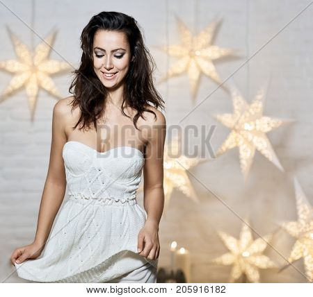 Beautiful happy woman in sleeveless knitted dress at christmas time.