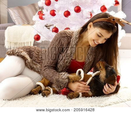 Woman caressing dog, lying on floor by christmas tree.