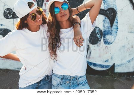 Two models wearing plain white t-shirts and hipster sunglasses posing against street wall. Teen urban clothing style, same look. Mockup for tshirt print store.