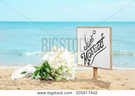Wooden board with text JUST MARRIED and beautiful bouquet on seaside. Beach wedding concept