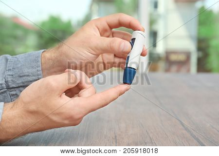 Man taking blood sample with lancet pen outdoors. Diabetes concept