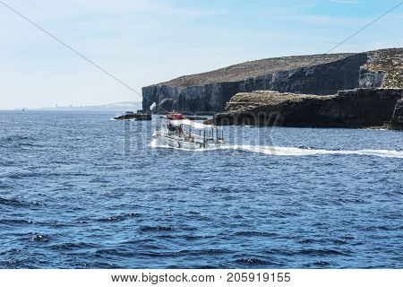 Comino is a small island of the Maltese archipelago between the islands of Malta and Gozo in the Mediterranean Sea. Pleasure craft at the rugged coastline delineated by sheer limestone cliffs and dotted with deep caves
