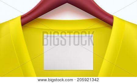 Yellow clothes and empty tag on the collar, wooden clothes hangers. Horizontal template for advertising of sales or new arrivals. Place for your text on white tag on clothing.
