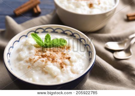 Creamy rice pudding with cinnamon powder in bowl on table, closeup