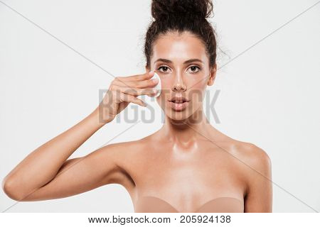 Close up beauty portrait of a pretty young woman with soft healthy skin removing make up with cotton pad and looking at camera isolated over white background