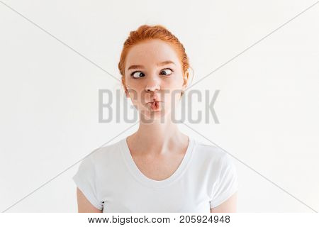 Funny ginger woman in t-shirt showing grimace over white background