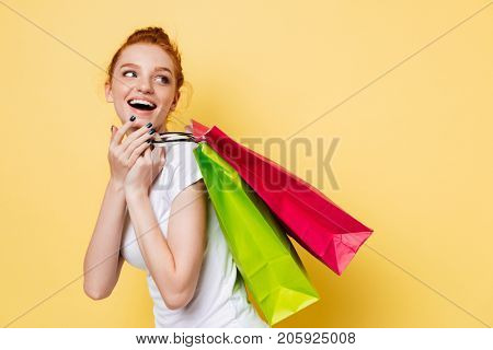 Side view of laughing ginger woman holding packets on shoulder and looking back over yellow background