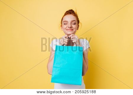 Pleased ginger woman holding packet in hands with closed eyes over yellow background