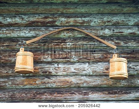 Ancient Russian yoke with buckets. Hanging on the wall of a wooden house.