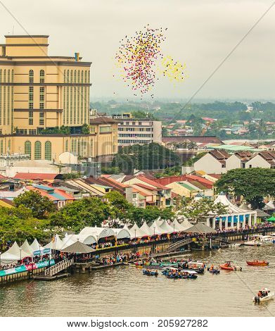 Sarawak Kuching Water Festival in november 2016, where a lot of ballons are released to the sky. Picture taken from above, showing people, city, river, boats and ballons against the sky.