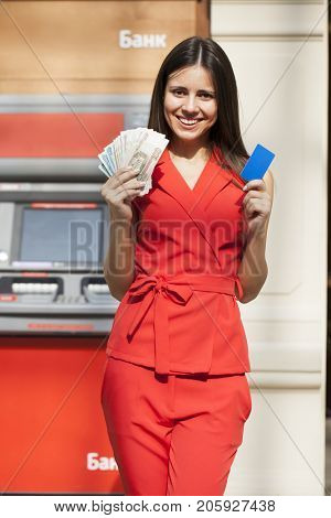 Young happy brunette woman withdrawing money from credit card at ATM. The inscription in Russian
