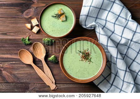Composition with tasty broccoli soup on wooden background