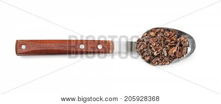 Spoon with cacao nibs on white background