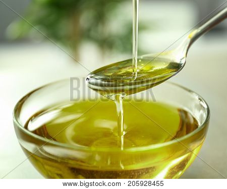 Pouring hemp oil into glass bowl on blurred background