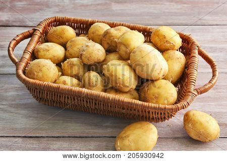 Wicker basket with young potatoes on wooden table