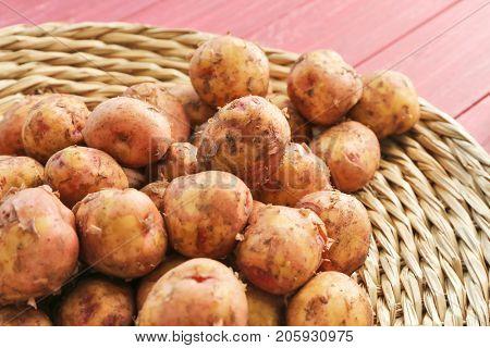 Young potatoes on wicker mat, closeup