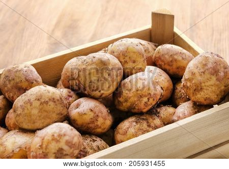 Wooden crate with young potatoes, closeup