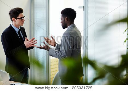 Young intercultural employees having talk in office after work