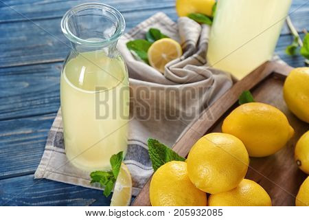 Composition with bottle of lemon juice and fresh lemons on table