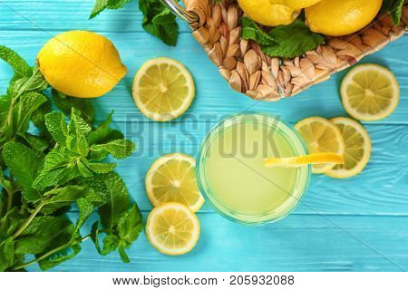 Glass of lemon juice, fresh lemons and mint on blue table